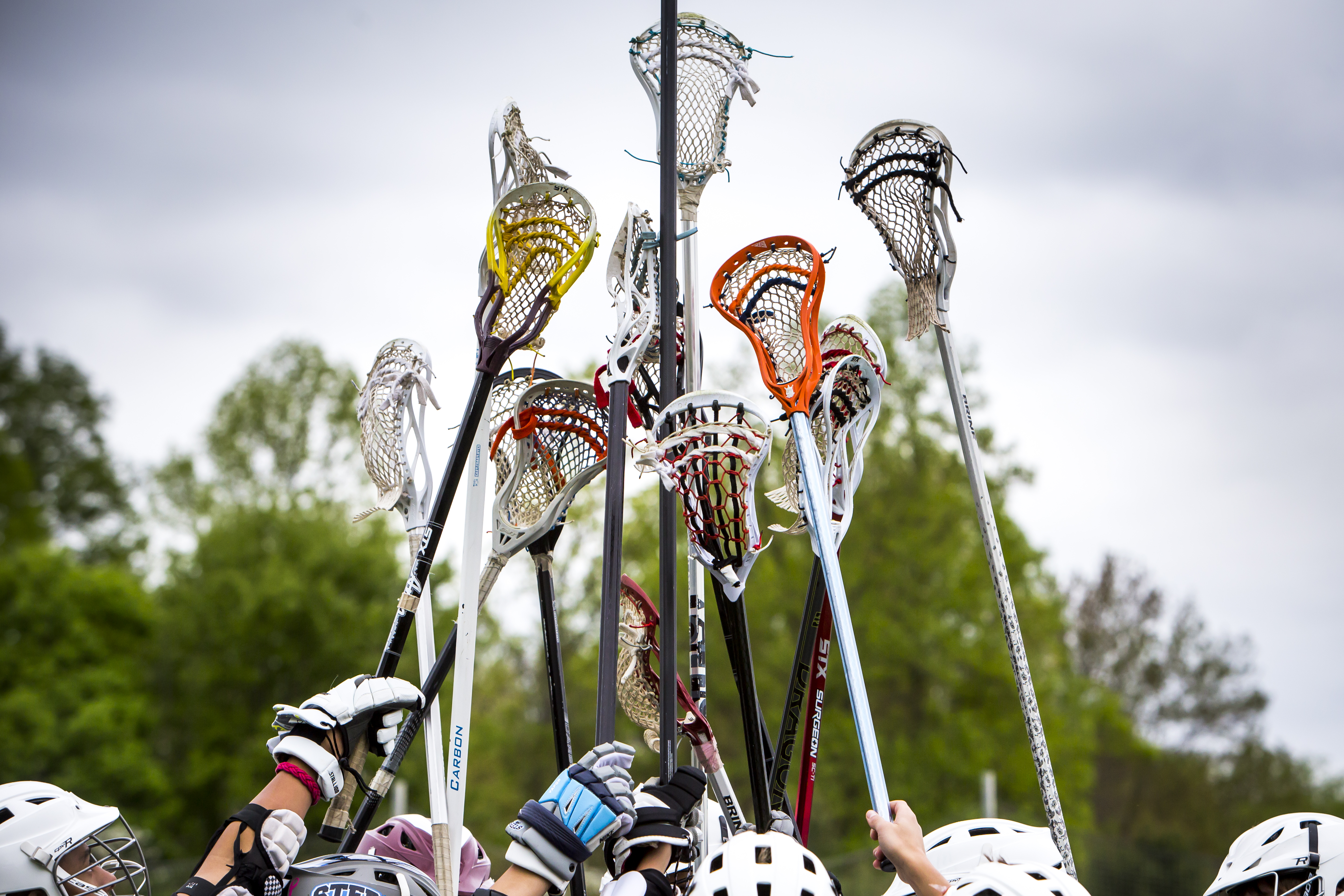 Boys lacrosse raising lacrosse sticks in air together in circle
