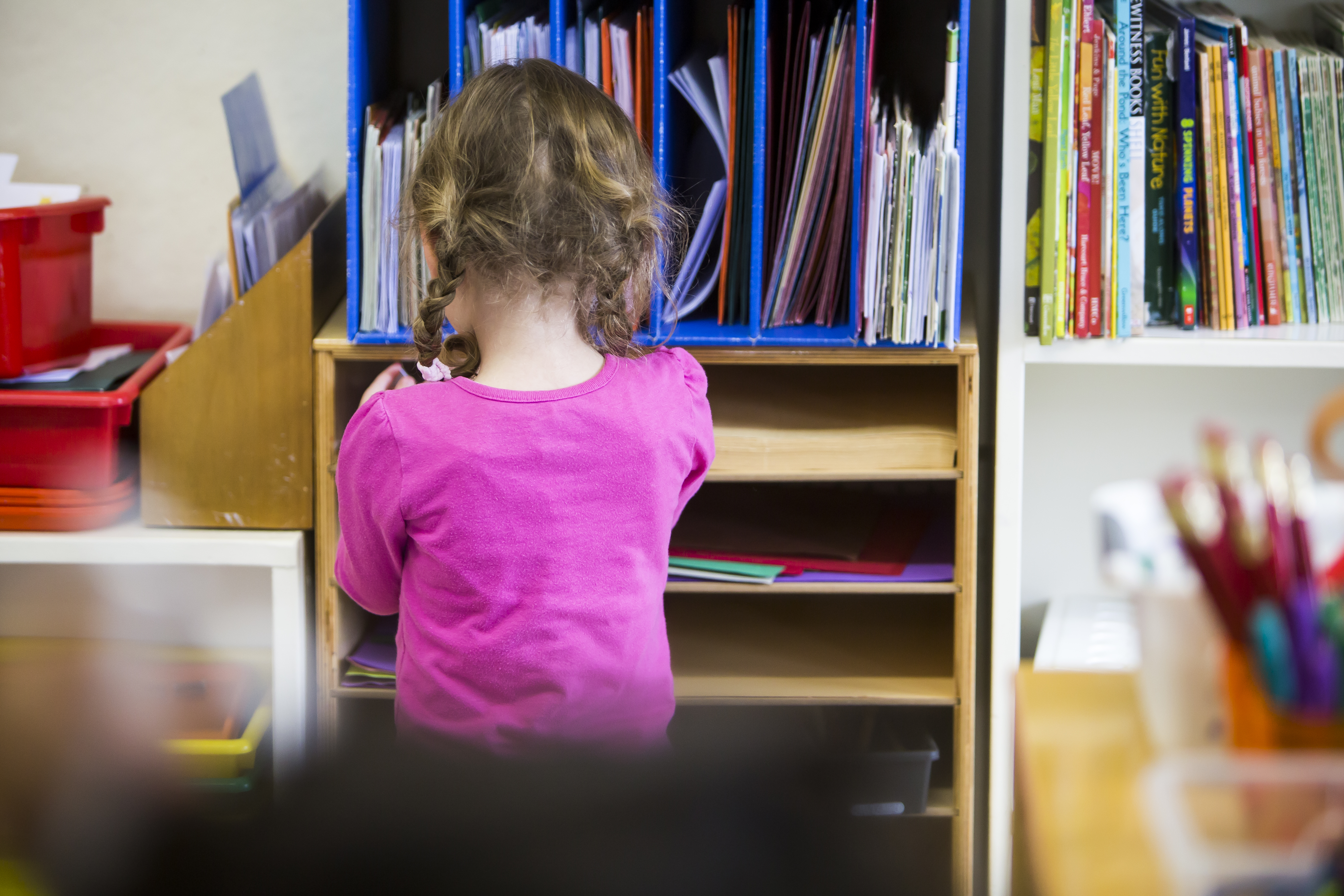 kindergarten girl looking through books